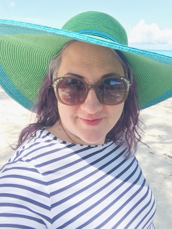 Carissa Bonham wearing wide brimmed hat and striped rash guard on the beach in Turks and Caicos