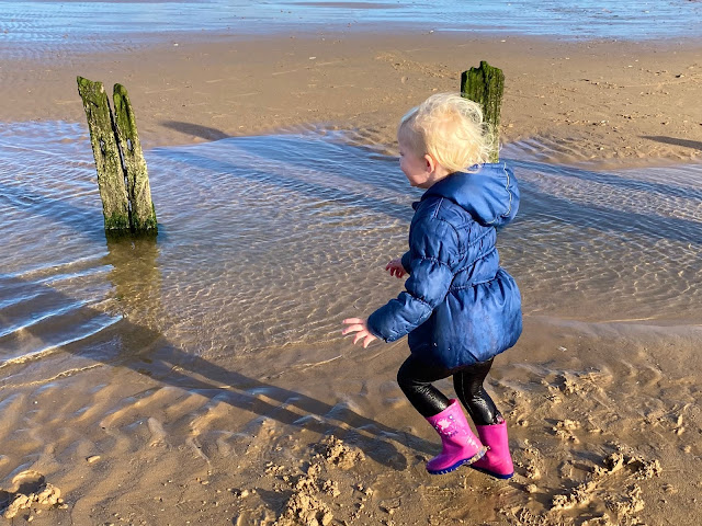 A 3 year old running around on the beach with very wet trousers and water sploshing out of the back of one of them