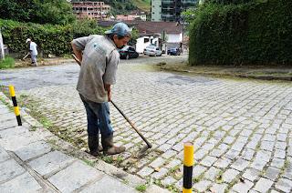 Em Agriões, funcionários se dividem entre as ruas Ipojuca e Yamato com pás, enxadas, roçadeiras e vassouras