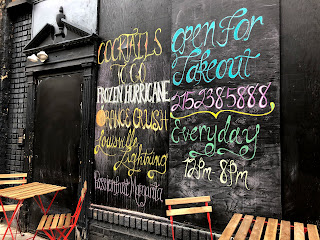 A boarded up restaurant with a chalkboard menu of cocktails to go.