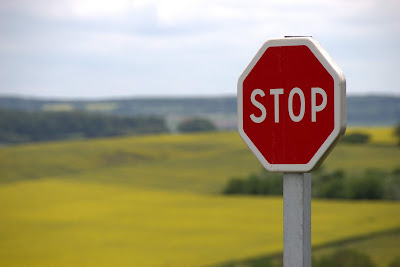 A  red stop sign on the side of the road