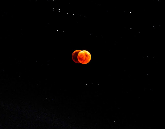 Double image of a red-orange moon on a black sky with scattered specks of stars