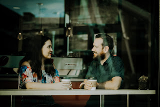 A man and woman making eye contact, while sitting in a cafe.