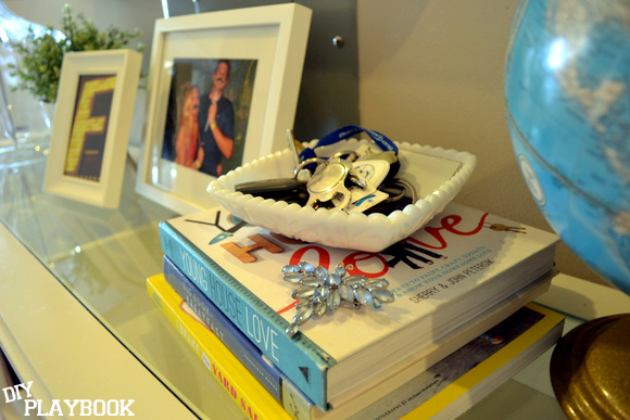 Keys in a white bowl on entryway table white picture frames books