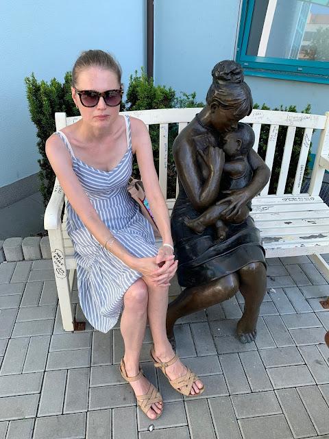 Linda sedí na lavičce vedle sochy matky s dítětem