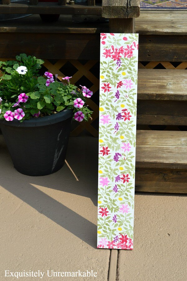 Stenciled Floral Board leaning on wooden deck next to flower pot