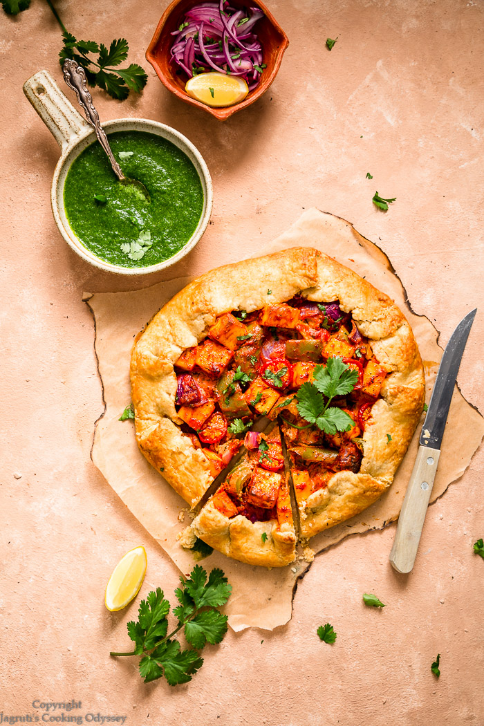 A slice of tandoori paneer galette next to whole galette and a knife on a paper.