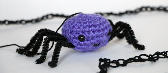 Purple amigurumi spider with black pipe cleaner legs and loosely crocheted web on a white background.