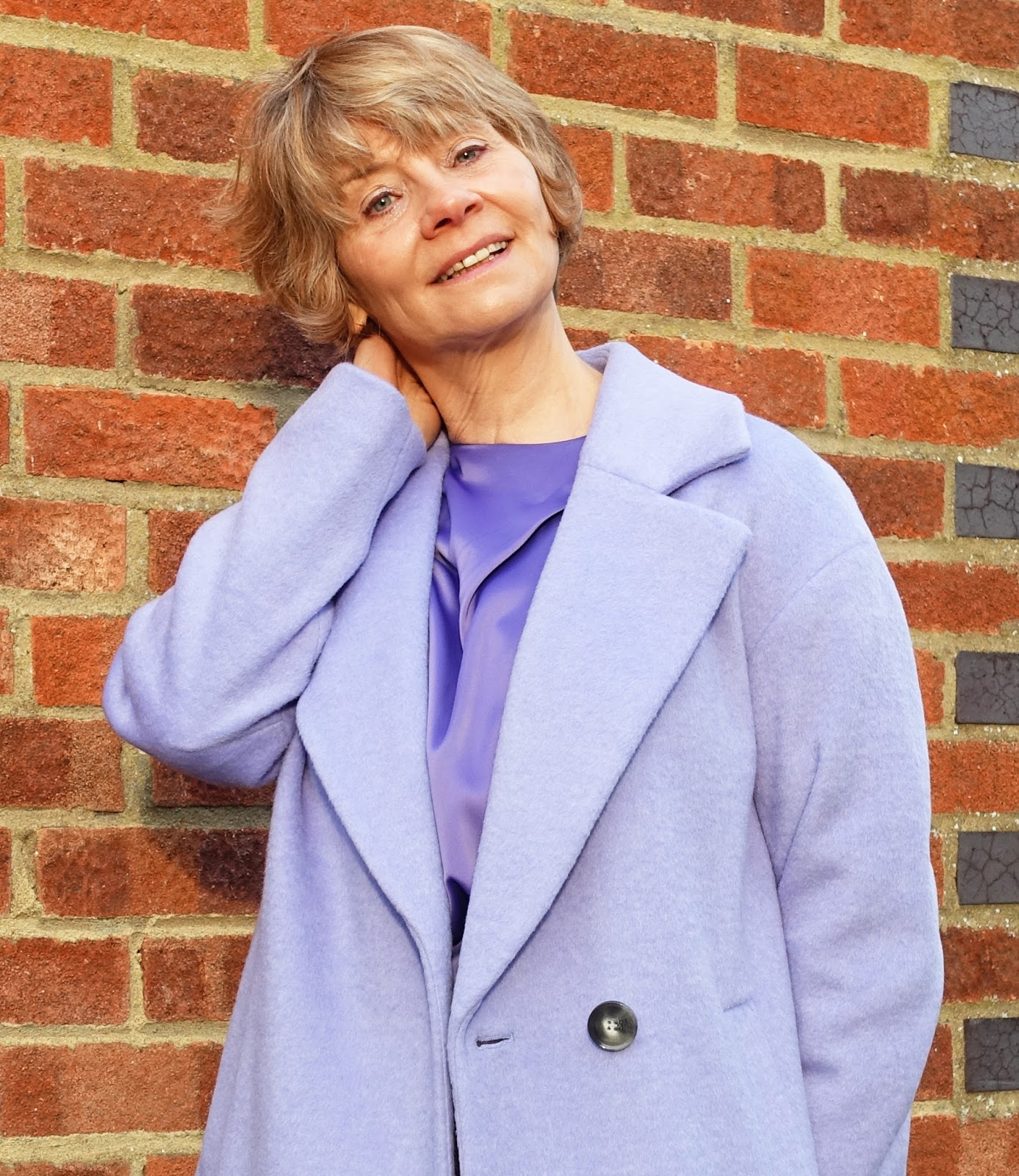 Image showing  a woman with blonde hair over 45 wearing a long wool coat in lilac