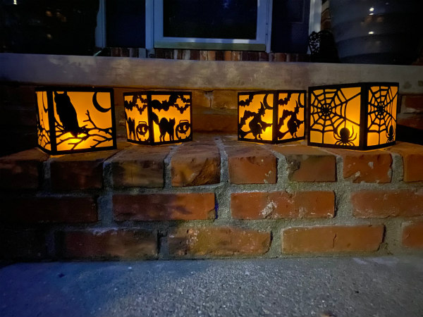 four Halloween theme luminaries on brick step
