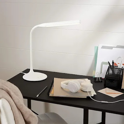 led desk lamp on top of table with book
