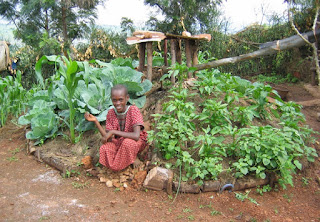 A girl in Rwanda sits in front of crops growing in a keyhole garden.