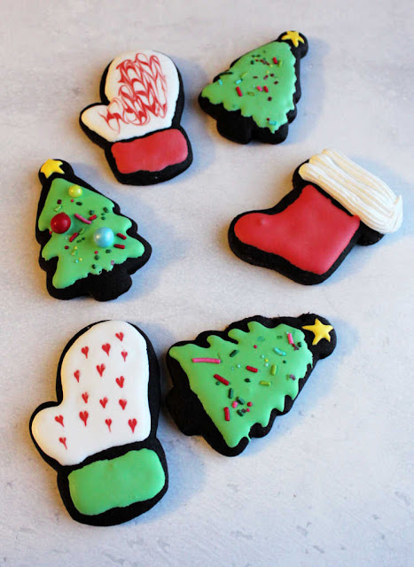 dark chocolate cookies cut into Christmas shapes and decorated with royal icing
