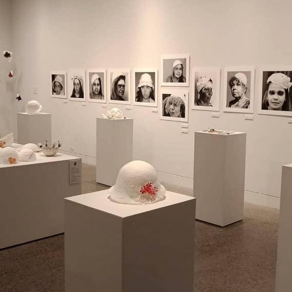 paper art exhibit featuring photographs of Aboriginal women wearing tissue paper hat sculptures