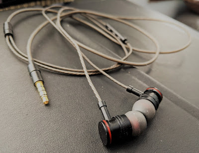 A pair of ear-buds that are connected by a typical wire plug in.