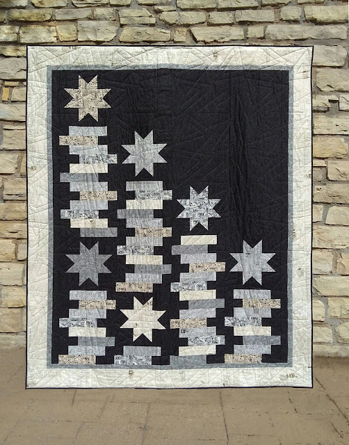 Quilt featuring stacks of rectangles and a few accent stars, all in creams and grey on a black background