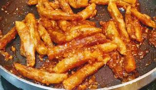 Stir frying potato fingers with honey chilli sauce for honey chilli potato recipe