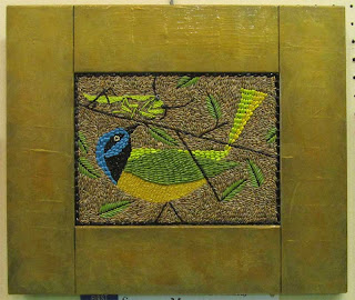 Colorful bird made from seeds with gold painted wooden frame