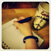 Photo of my hand, writing on a spiral bound journal; next to it, a coffee cup with a peace sign on it.