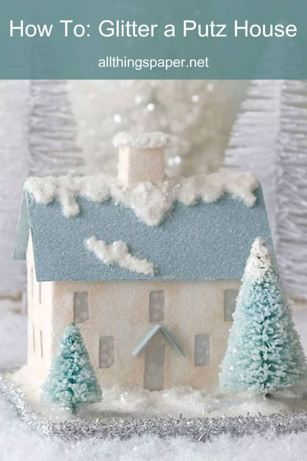 tiny paper putz house decorated for winter with glittered snow drifts
