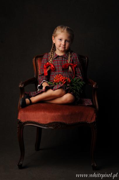 Sesja dziewczynki w warkoczykach z jarzębiną na starym stylowym fotelu