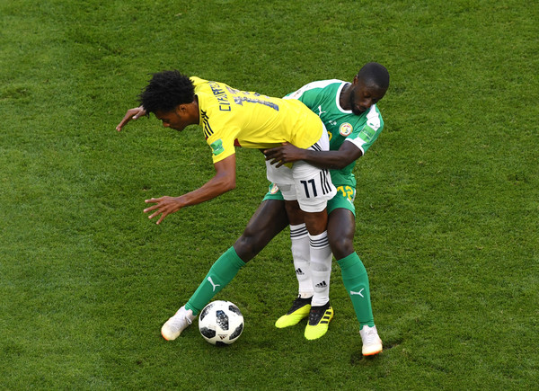 Youssouf Sabaly of Senegal tackles Juan Cuadrado of Colombia during the 2018 FIFA World Cup Russia group H match between Senegal and Colombia at Samara Arena on June 28, 2018 in Samara, Russia.