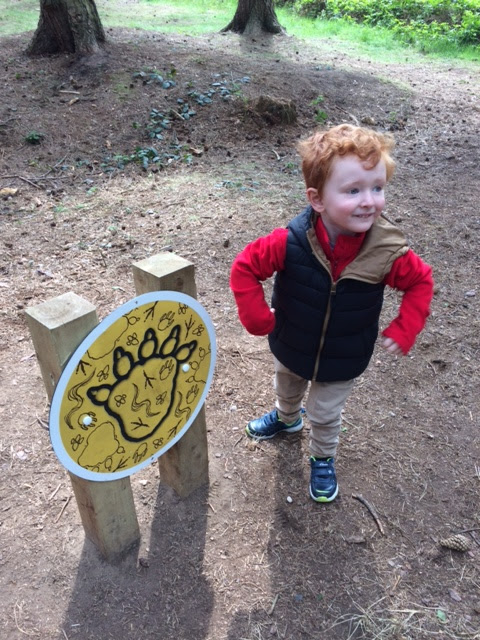 Little boy with his hands on his hops next to a footprint sign