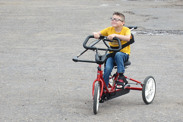 action photo of boy smiling on therapeutic trike