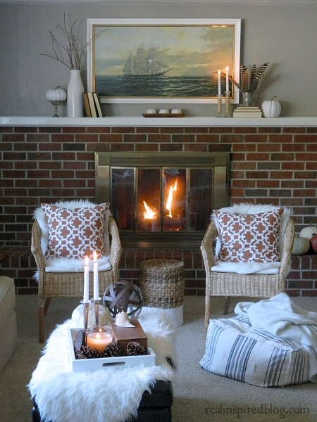How to Decorate a Long Mantel for Fall/Autumn: sticks, white pumpkins, orange pillows, nautical, ship, art, books, feathers, brick fireplace. candles