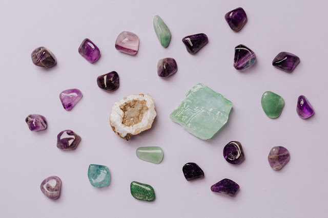 Gemstones shot flatlay style against a lavender backdrop.