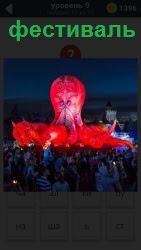 На фотографии демонстрация фестиваля с поднятием красного шара и большого количества людей