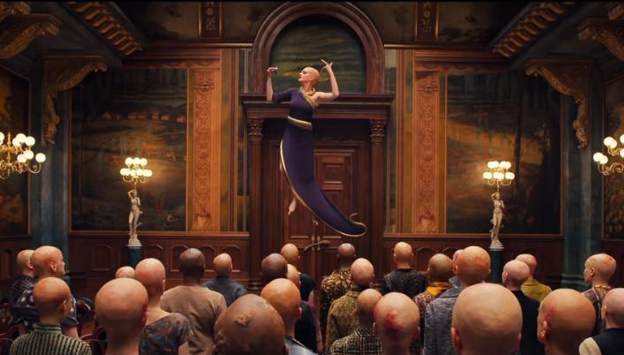 Imagem: a Grande Bruxa flutuando sobre as bruxas no salão da convenção, todas elas são carecas e tem pequenas feridas nas cabeças, e a Grande Bruxa, está segurando um pequeno frasco arroxeado.