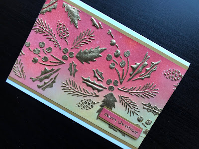 Christmas card with heat embossed stencilling on an inked background.
