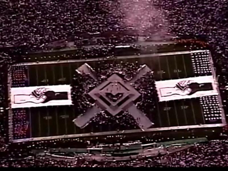 ステージの両側に広げられた握手する白人と黒人の手の二つの巨大な絵