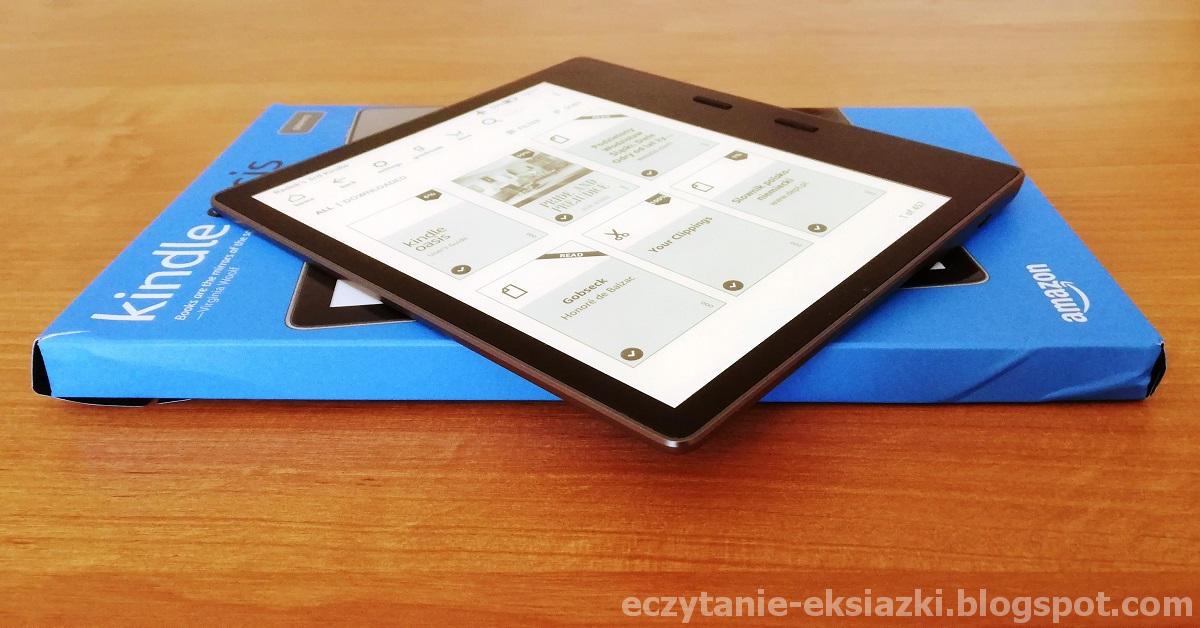 Kindle Oasis 3 z włączonym podświetleniem, położony na opakowaniu