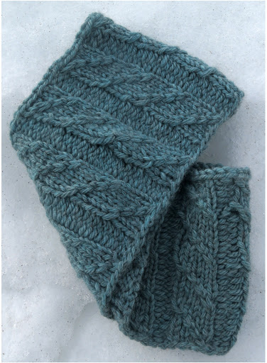 a cowl knit in light-blue worsted weight yarn, with a cable that crosses columns of knit stitches.