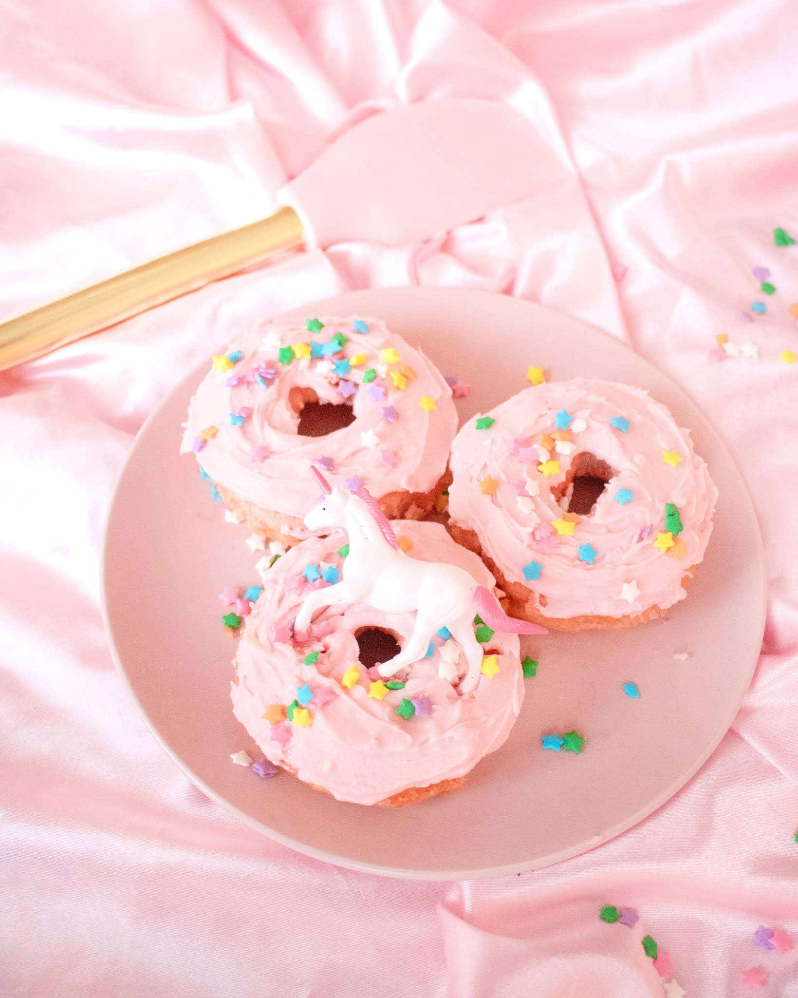 Doughnuts on a plate on a pink fabric background