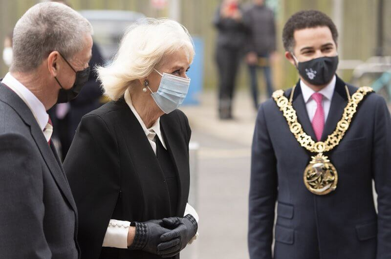 The Duchess wore a black cape and pearl earrings