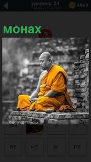 Около каменной стены сидит монах молча в желтой одежде сложив руки на коленях