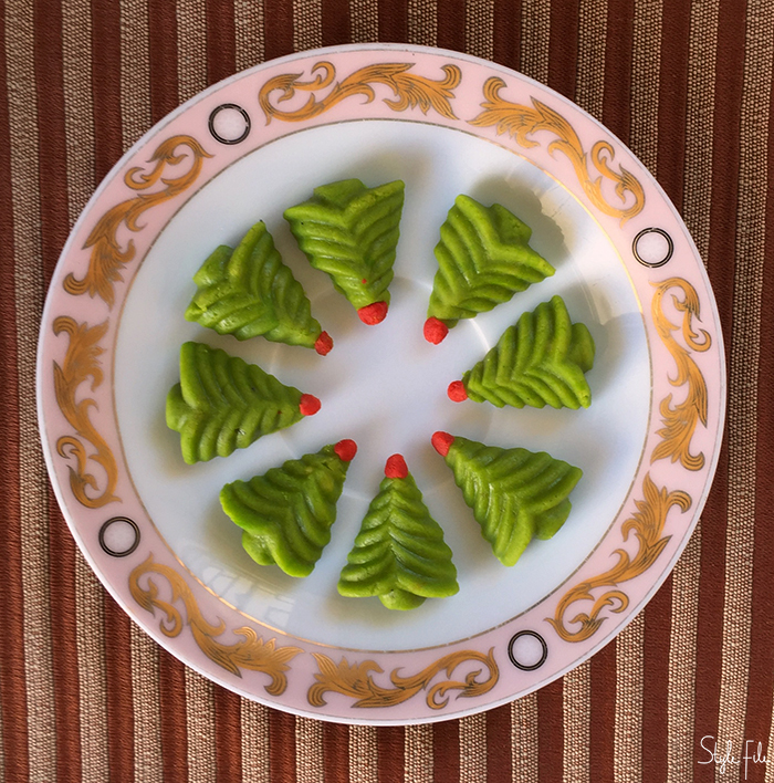 Image of marzipan Christmas sweets in the shape of Christmas trees on a glass plate