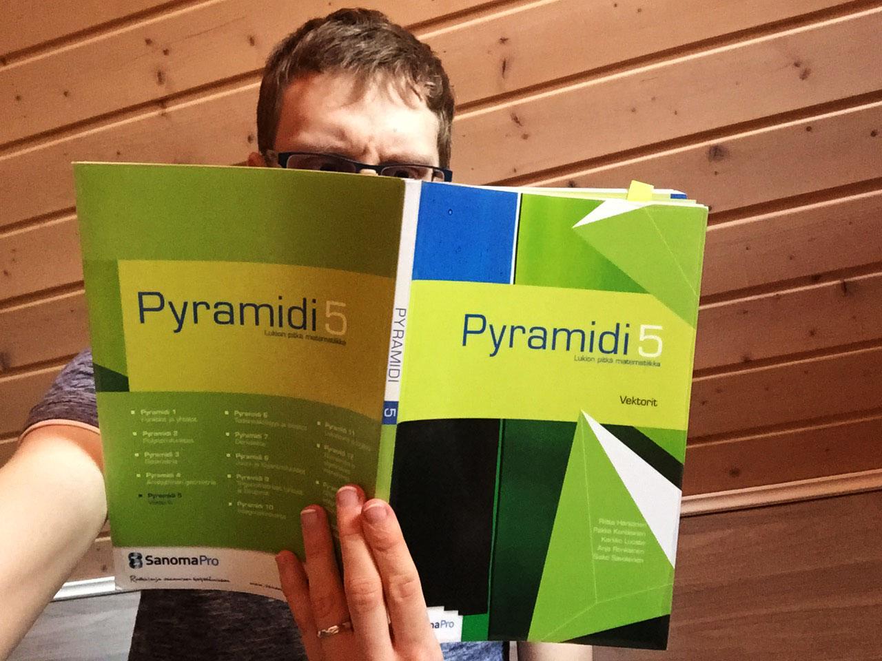 Minä lukemassa Pyramidi 5 -oppikirjaa vektoreista.