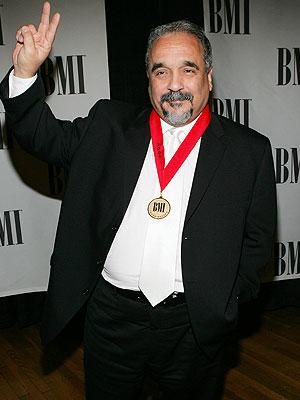 Foto de Willie Colón con traje negro y corbata blanca