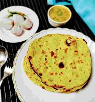Serving Missi roti in a plate, onion , green chili and dal in background