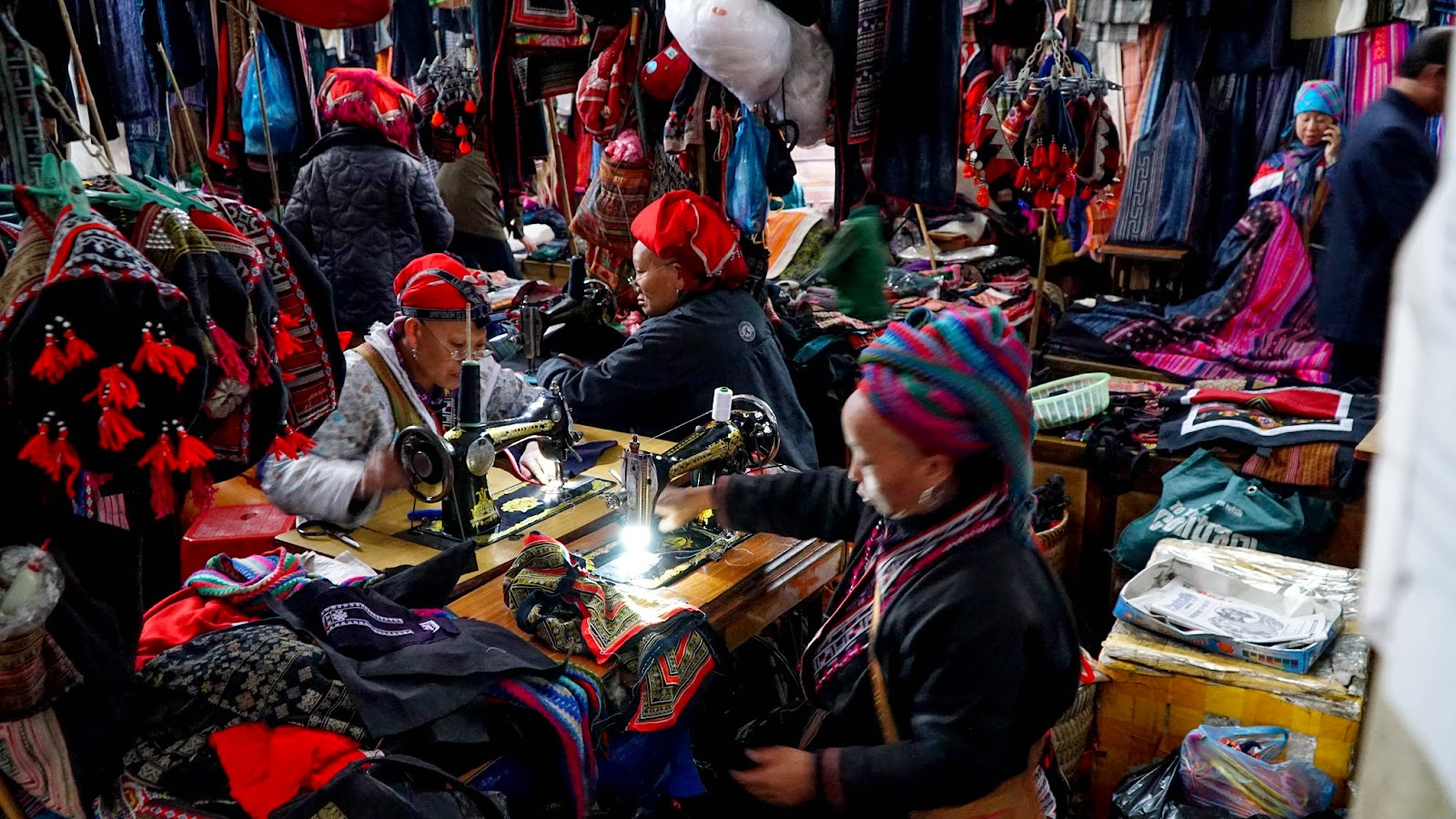Busy Hmong ladies at work in the market. Some offer to personalize your souvenirs if you buy from them