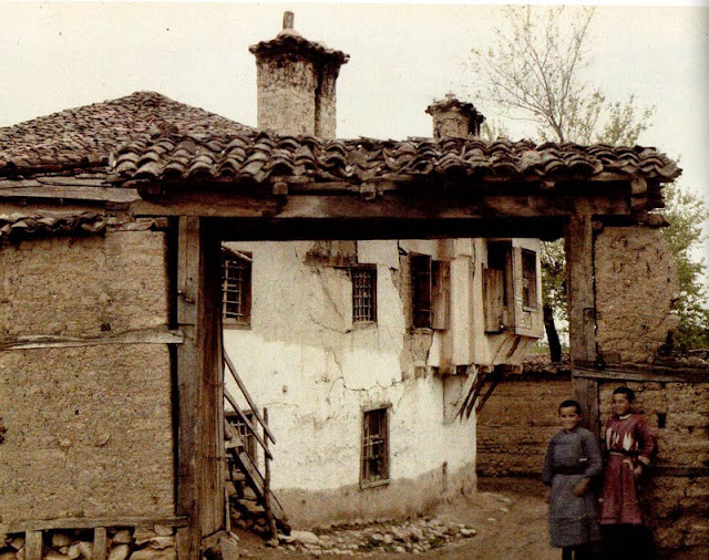 A traditional orthodox house (a front door) with a corbelling. Two little boys dressed in tunics. - - Macedonia in 1913
