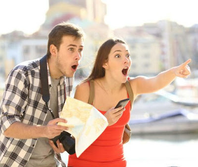 A man and woman with a surprised look on their faces, she is pointing forward and he is holding a map.