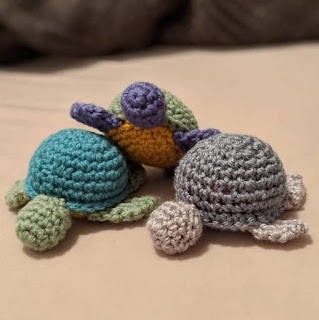 Three small crochet turtles nestled together