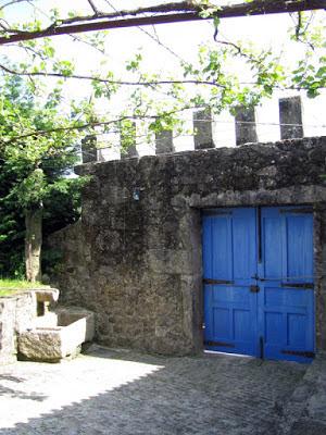 muro de pedra e uma porta de madeira azul