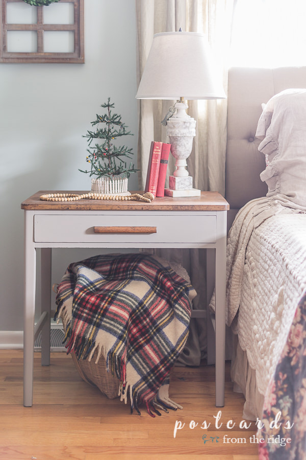 plaid throw blanket in large woven basket underneath night stand