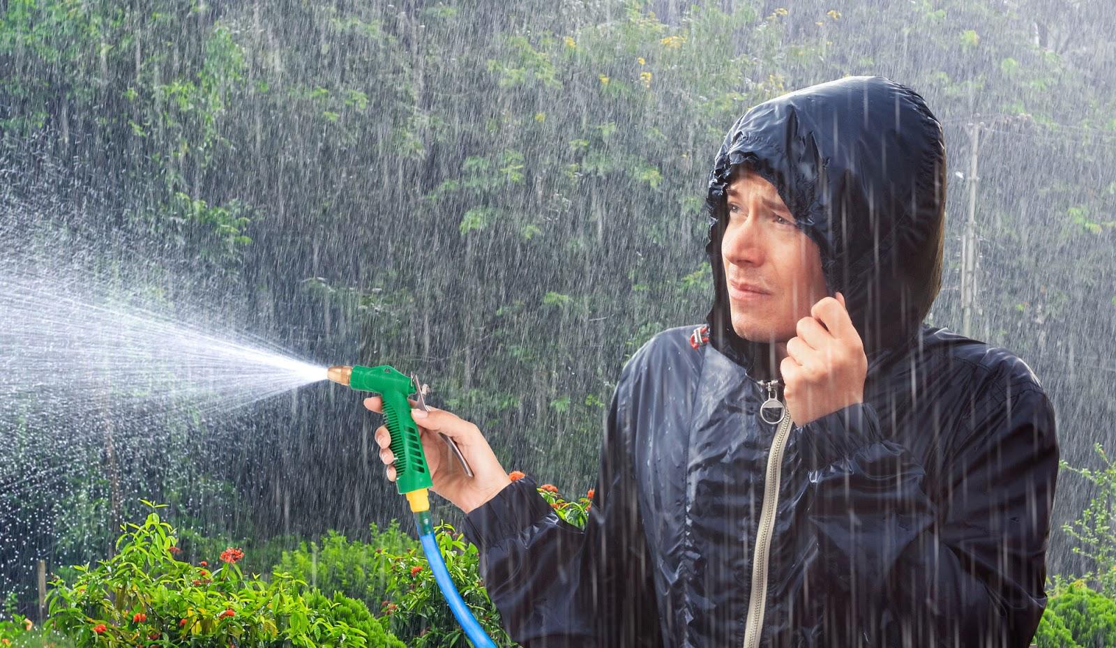 Weil es in Strömen regnet: Mann muss beim Gartengießen Regenjacke tragen